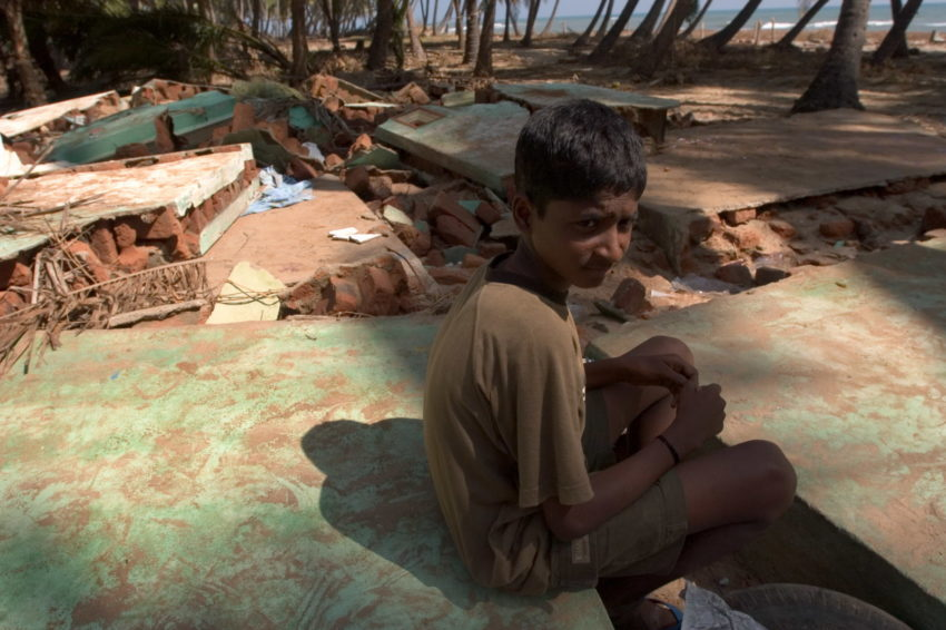 After the 2004 Indian Ocean tsunami hit the coast of Tamil Nadu state in southeast India, Booplan Raman, 15, sat next to his destroyed home. Debris is all that's left of his family's possessions. Booplan's father, mother, and four siblings survived, but are struggling to get by on relief supplies.