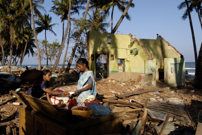 In the days after the 2004 Indian Ocean tsunami devastated the coast of India's Tamil Nadu state, two young women sift through the remains of their home looking for valuables and documents. Many coastal dwellers lost their livelihoods as fishermen and fish mongers when the waves destroyed their homes, boats and nets.