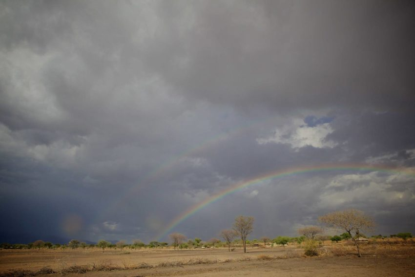 A double rainbow appears over a village in Tanzania.