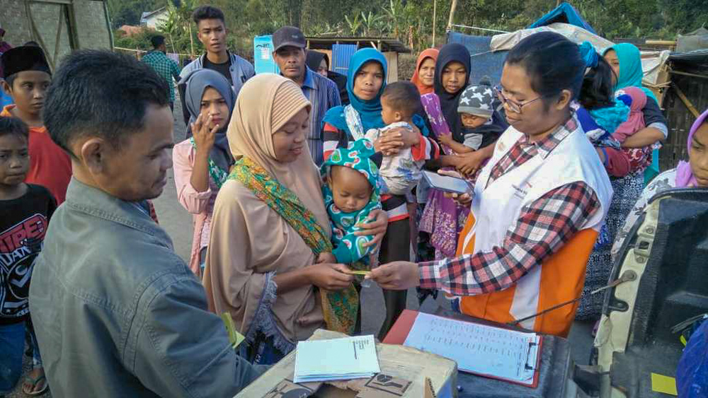 A World Vision aid worker helps distribute emergency relief supplies to people affected by the earthquake and tsunami in Lombok, Indonesia.