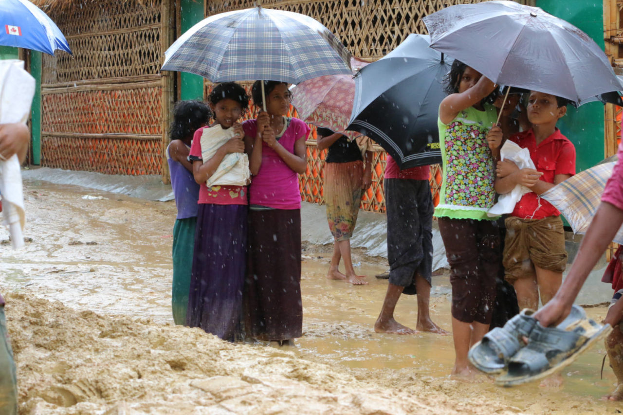 Children huddle together under an umbrella in the middle of a muddy street in a refugee camp in Cox's Bazar, Bangladesh. Monsoon rains throughout 2018 caused an increased risk of landslides and water-related diseases such as diarrhea and cholera.