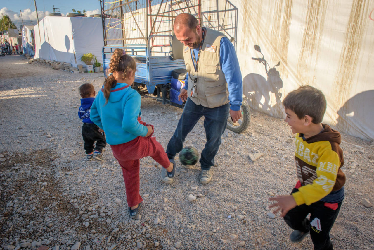 A World Vision staff member plays soccer with Syrian refugee children in the informal tented settlement where they live. Lebanon has approximately 3,000 informal refugee settlements in the country.