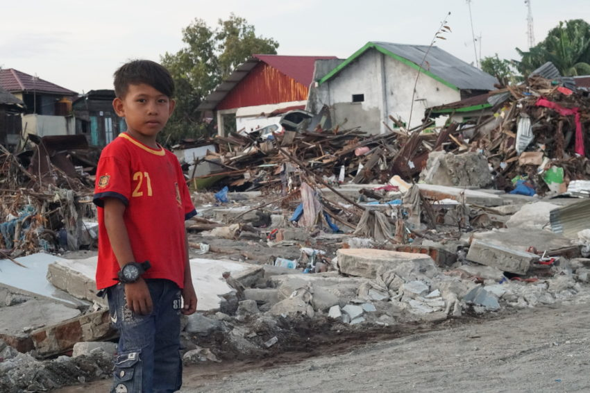 A week after the September 28 Indonesia earthquake and tsunami in Central Sulawesi, Alif, 9, stands amid debris. When the quake hit, Alif and his family ran for the hills. The quake and tsunami leveled much of Palu city and Wani Port, where Alif lives.