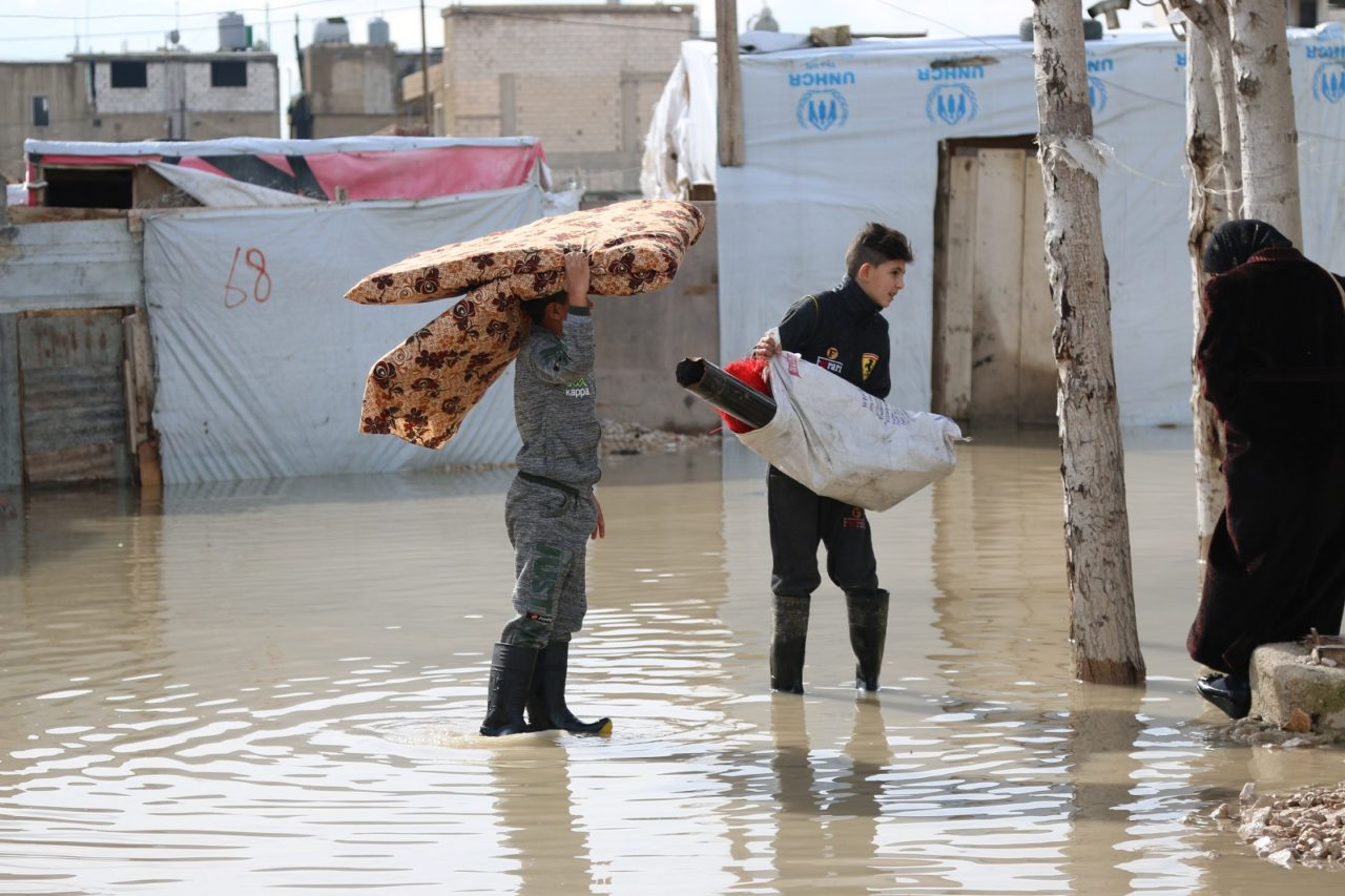 Syrian refugees in Lebanon affected by a winter storm in January 2019. Boys carry bedding and other salvaged goods from their flooded shelters after a winter storm brought rain and snow to a tent settlement. Many Syrian refugees have been flooded out of their shelters and lost all their possessions.