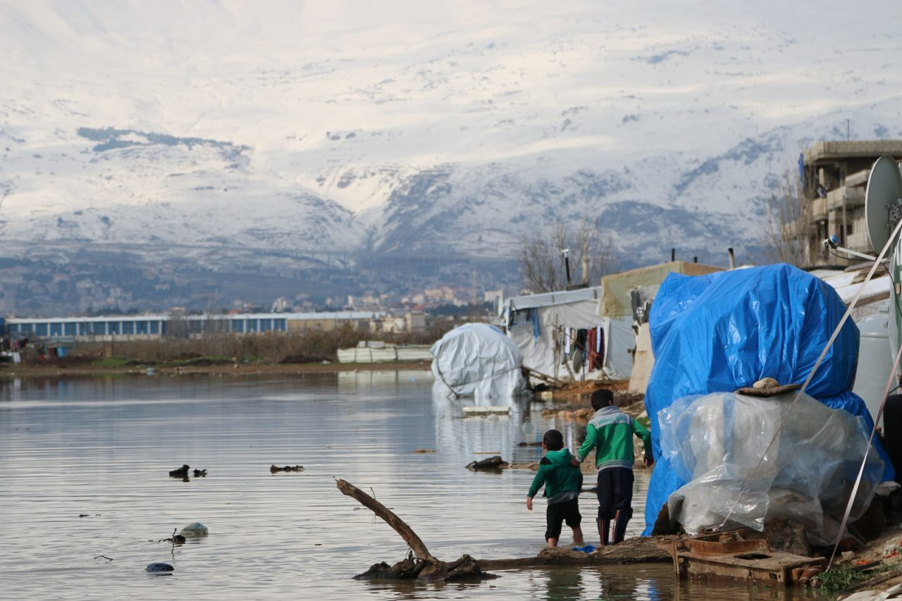 Syrian refugees in Lebanon affected by a winter storm in January 2019. Children walk through a flooded tent settlement in Lebanon's Bekaa Valley. Many Syrian refugees have been flooded out of their shelters and lost all their possessions.