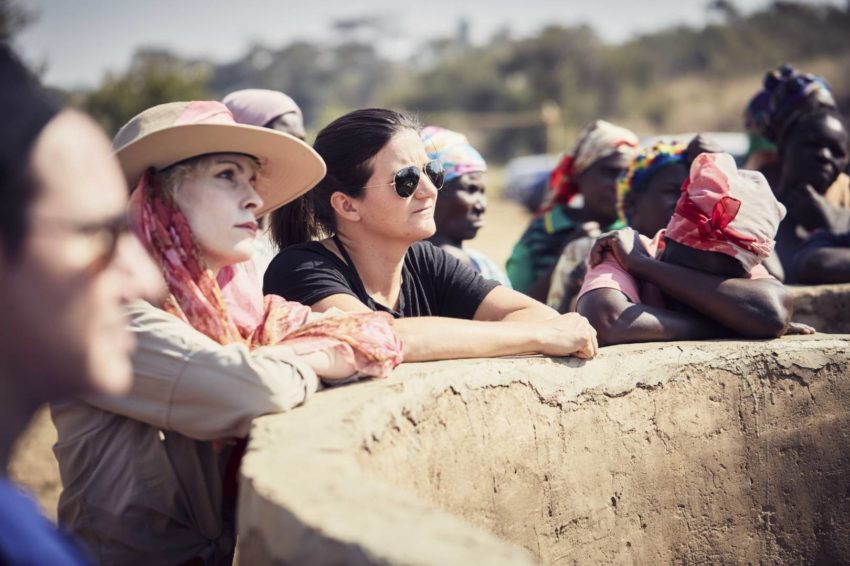 Olympian snowboarder Kelly Clark stands by a water pump in Zambia.