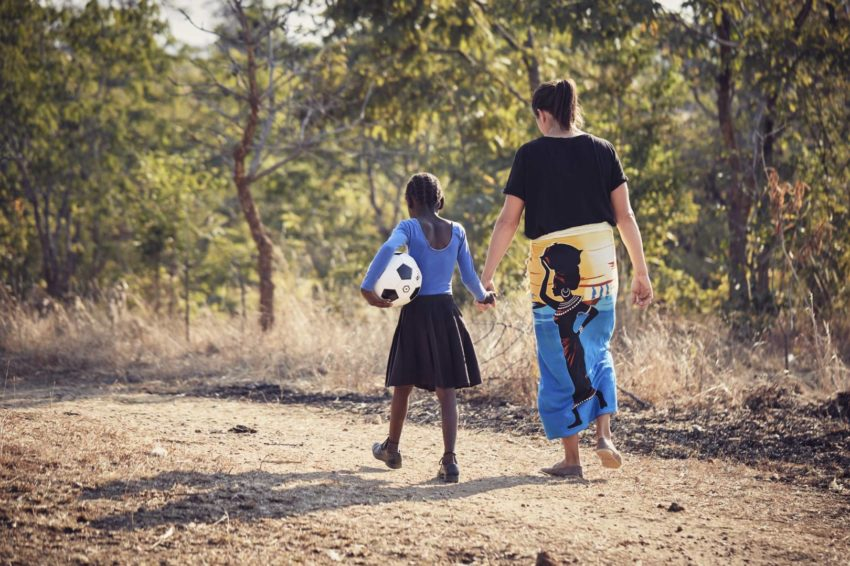 Olympic snowboarder Kelly Clark walks down a dirt path with her sponsored child.