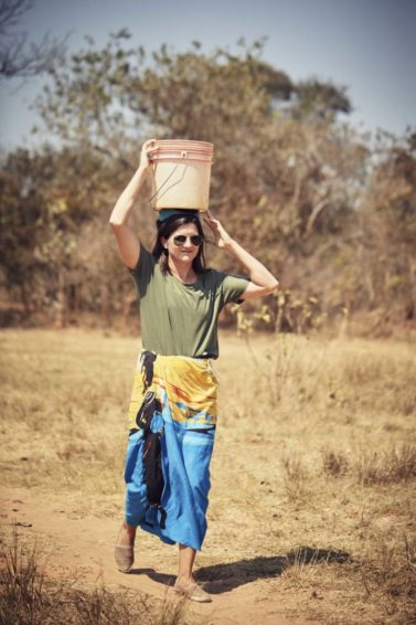 Olympic snowboarder Kelly Clark carries water on her head in Zambia.