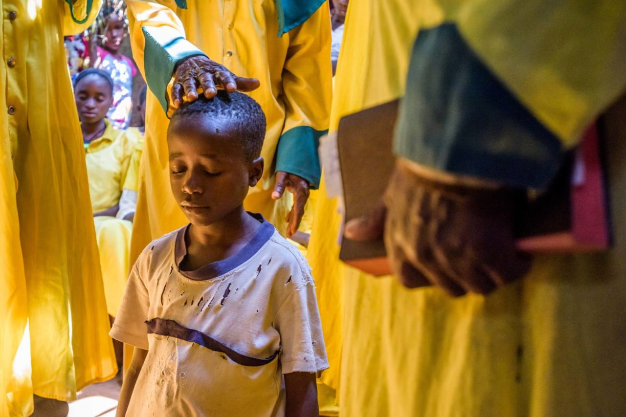 A boy receives blessings at church in the DR Congo