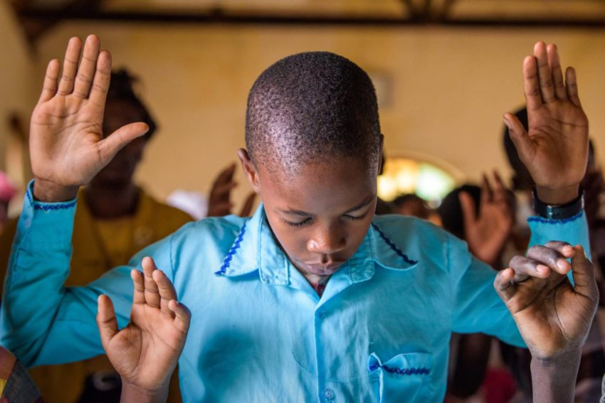 A boy worships during church services in Kenya.