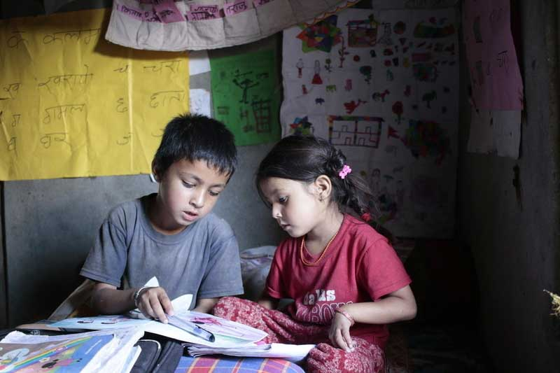 Jhalak, left, reads with his sister at the reading corner his family created in their home in Nepal. Reading corners are part of the literacy program World Vision created to increase literacy rates in Nepal.