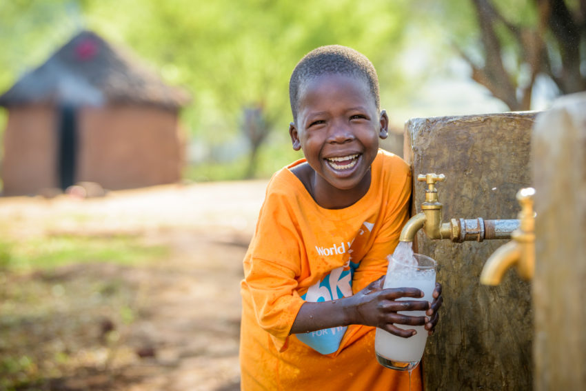 Happy Cheru, wearing a World Vision Global 6K tee-shirt, fills her glass at the water point at her home, and takes a drink of clean water. Cheru, 6, benefits from a 16-kilometer, gravity-fed World Vision pipeline that brings clean water to her community. Along with other children, she used to walk 6 kilometers daily to carry water to school and home. Now the pipeline brings water to both places.