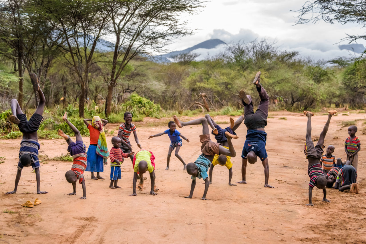 Children in Kesot village do handstands, Cheru and her friends do handstands, joined by Charles Kakiti, World Vision water engineer. Touched by the donors who funded the Kesot water project, Charles ran the Global 6K to bring water to children in other parts of the world.