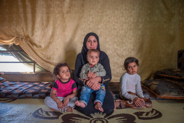 Syrian refugees in Lebanon informal tented settlement. Aysha, 29, a Syrian refugee in Lebanon's Bekaa Valley, sits inside the tent where her family lives since fleeing from Syria. Her children include (left to right) Islam, 2 ½; on her lap, Ahdy, 1; and Catherine, 5.