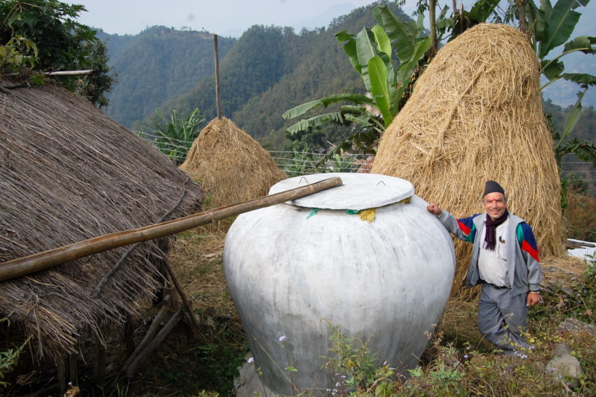Rainwater catchment in Nepal. Sri Ram Baral stands next to a white tank, known as a ghaintas, in Hansapur, Nepal. World Vision taught Baral how to build rooftop rainwater collection systems and how to create a greenhouse that allows his family to easily grow nutritious vegetables. Now his vegetables and gardens can flourish.