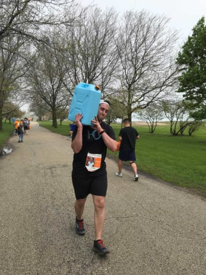 A HOH Water Technology employee carries a jerrycan of water at the 2018 Global 6K for Water.