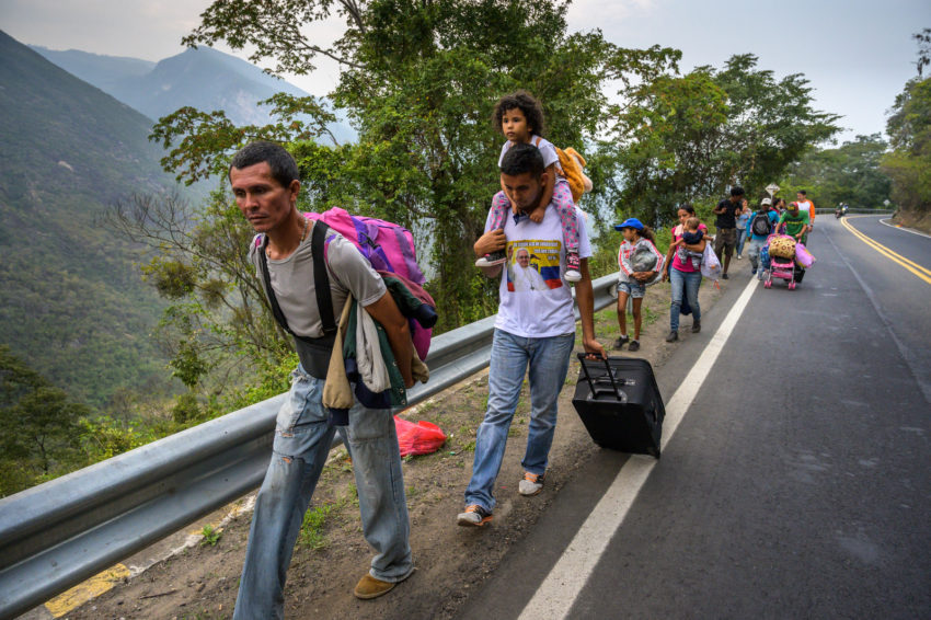 "Venezuelan migrants walk on the road in Colombia. Some had been on the road for 18 days before crossing into Colombia. For the next leg of their journey, they will climb the steep roadway to elevations of 10,000 and 12,000 feet where the temperatures can be below freezing, especially at night. Two of the children are under six-months-old. ""This is what happens when you can't make enough money to feed your family. You have to leave any way you can,"" says the group leader."