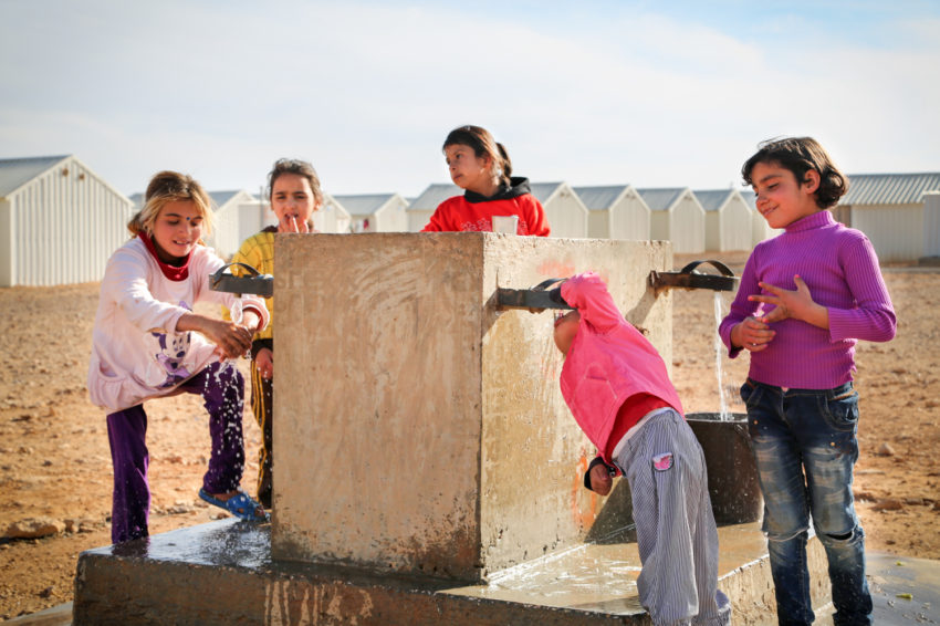 Syrian refugee children drink from water taps installed by World Vision at Azraq Refugee Camp in Jordan.