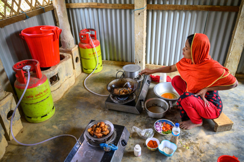 Woman cooks on a two-burner gas stove
