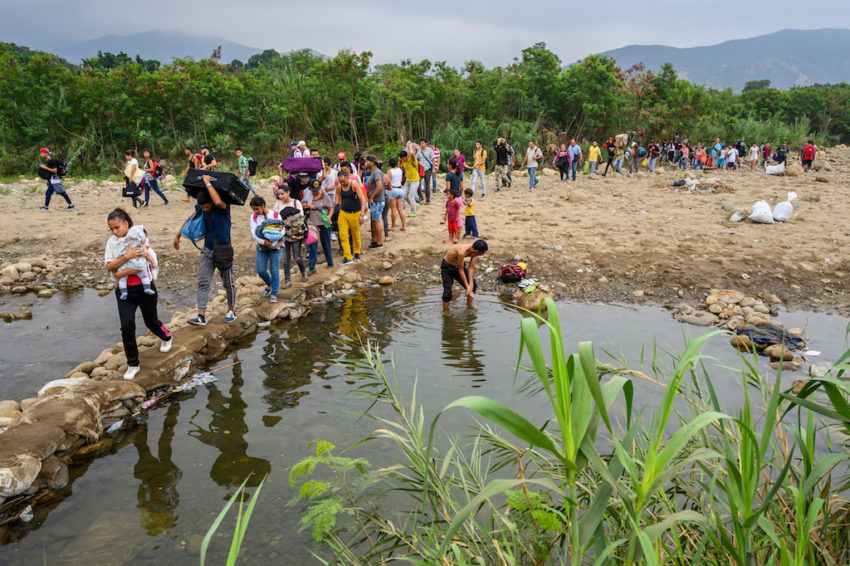 People walk away from Venezuela and across the Tachira River to Colombia.