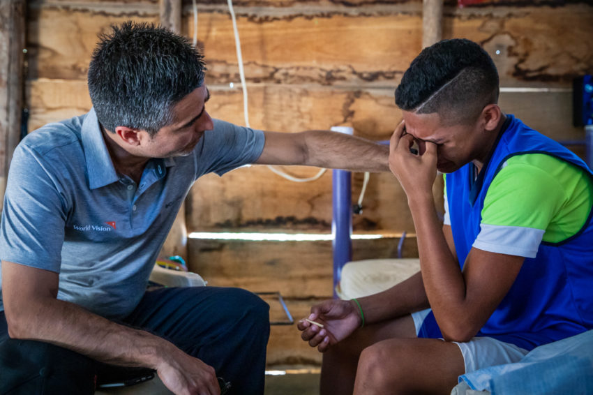 A man prays with a young man.
