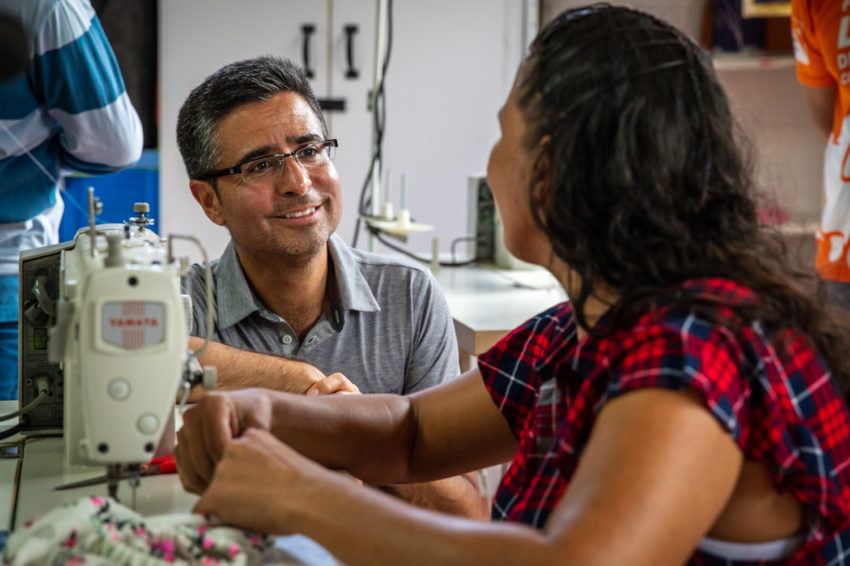 A man visits with a woman who works on a sewing machine.