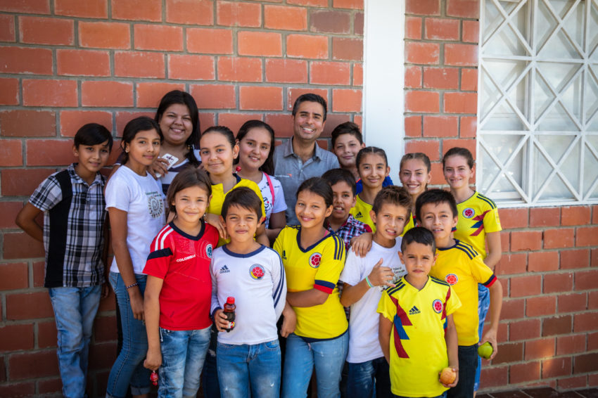 A man poses for a photo with a group of children.