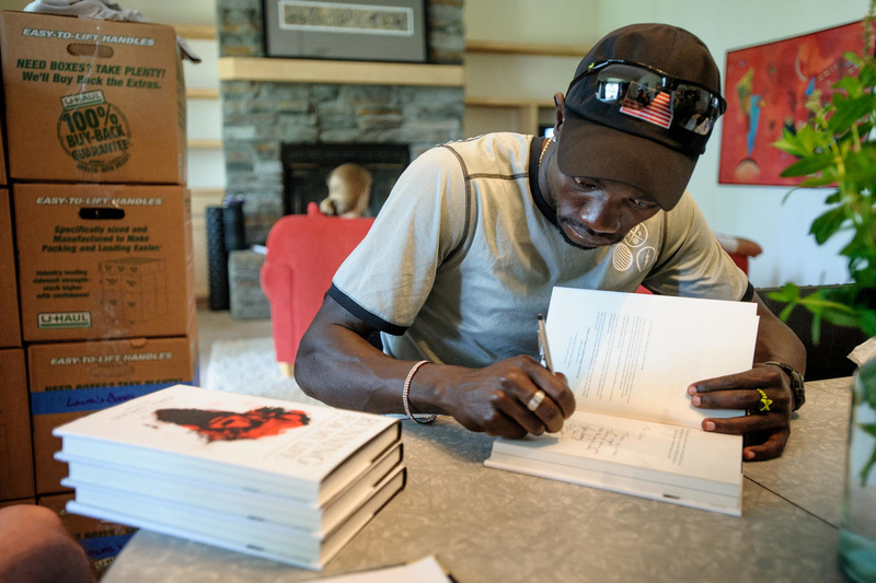 Lopez Lomong signs copies of his book, Running for My Life, which he wrote about his experience as a refugee.