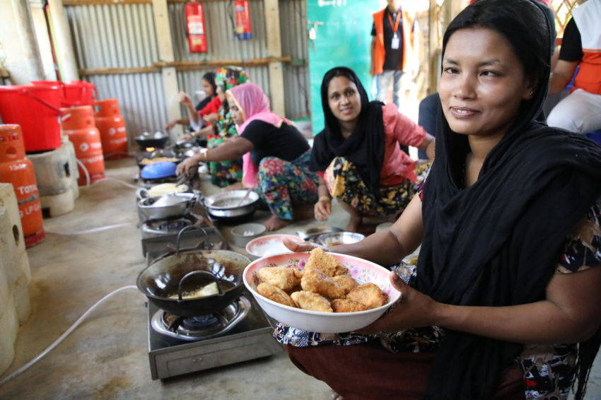 Refugees from Myanmar in Bangladesh. Mohsena, 18, cooks in one of 42 World Vision community kitchens in a Rohingya refugee camp in Bangladesh. The kitchens are community hubs where women can cook, learn new skills and find the support they need. Using gas cookers in the kitchens also prevents cooking fires in the refugees' small shelters and eliminates the need for gathering increasingly scarce firewood.