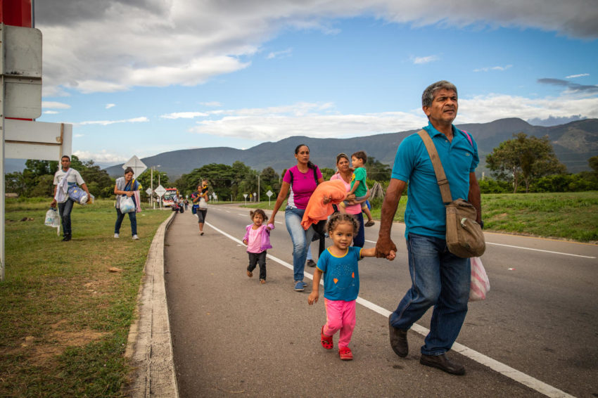 Venezuelan migrants walk along the road in Colombia. About 3.4 million Venezuelans have left the country because of hyperinflation, lack of medical supplies and food, as well as political instability.