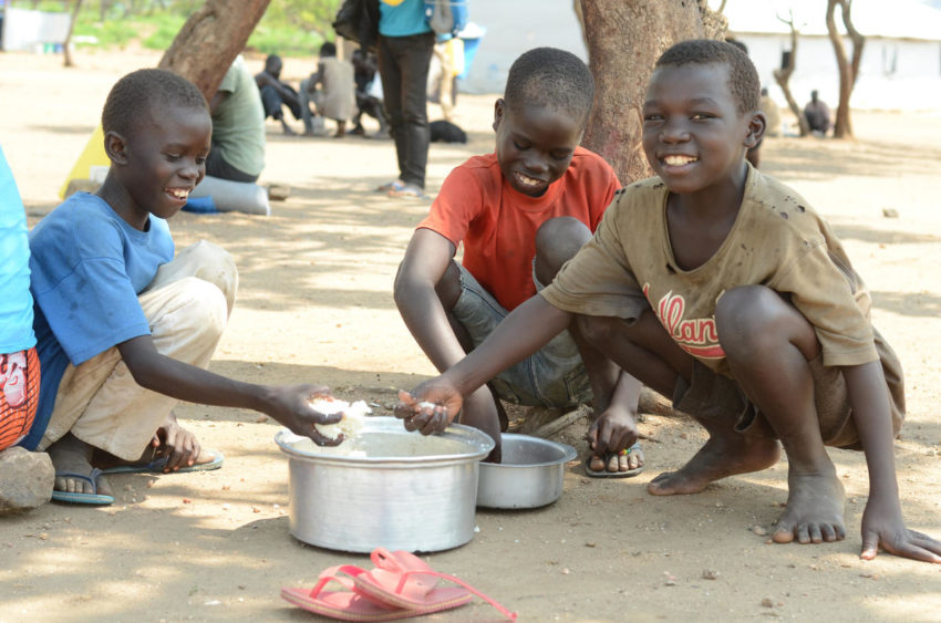 Refugees from South Sudan conflict and hunger. At Impevi refugee camp in Uganda, South Sudanese refugee Bosco, 11, (right) and his friends, Moses, 12, (in red) and Kibo, 10, eat a hot lunch of corn-soya blend and beans provided by World Vision. About 60% of the refugees who have fled South Sudan for Uganda are children. World Vision provides humanitarian assistance to South Sudanese refugees in Ethiopia, Uganda, and Kenya.