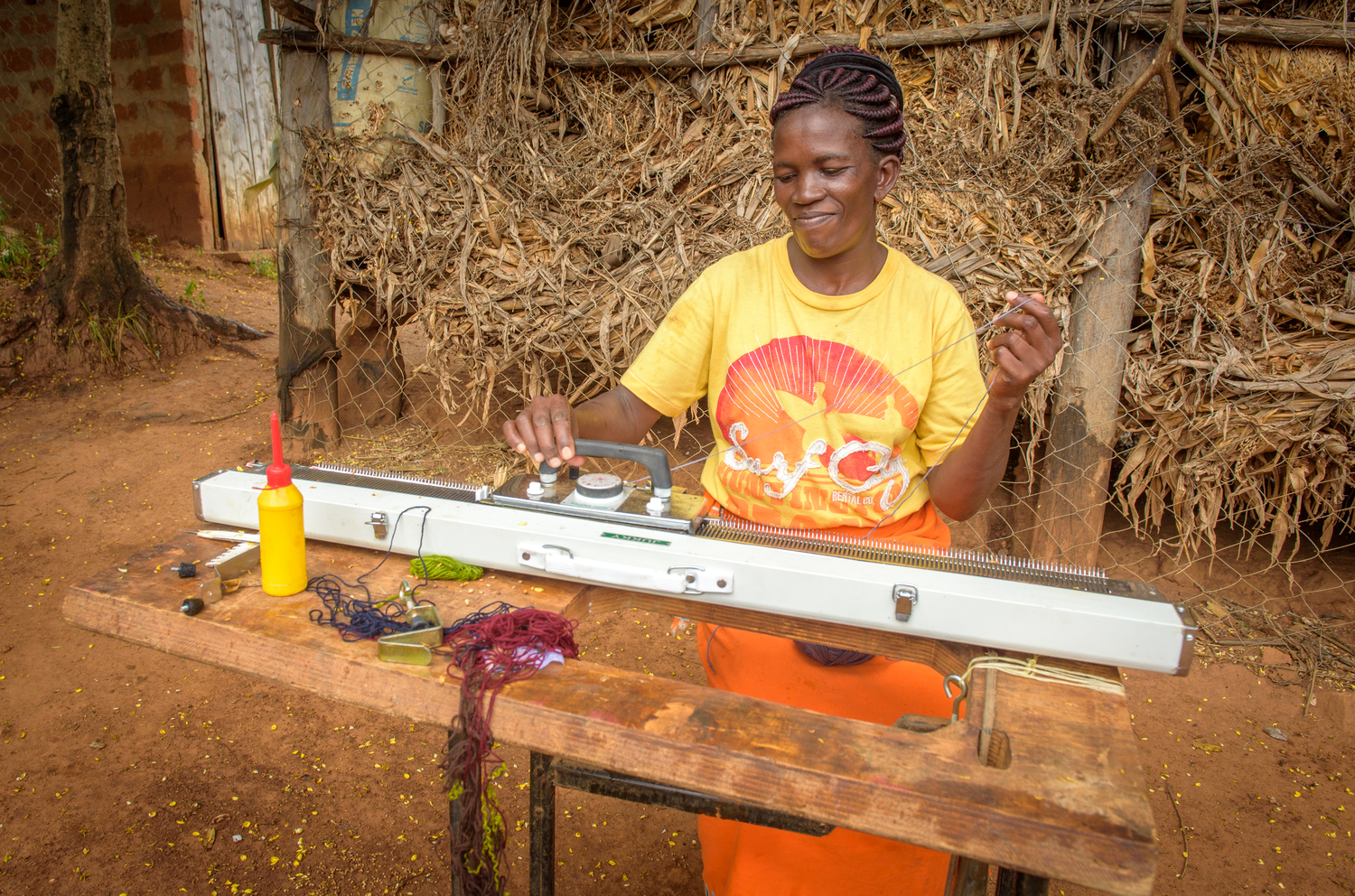 Janet now makes school uniforms on a new World Vision-donated knitting machine. This enables Janet to work from home so she can care for Cynthia.