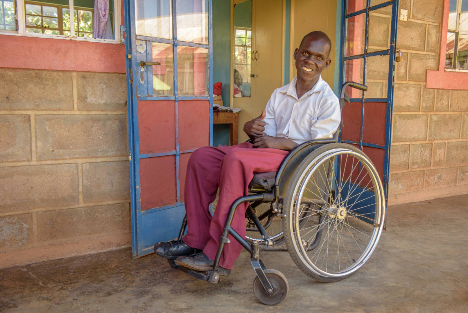 "Benedict sits outside his classroom in the wheelchair he received from World Vision through the USAID-funded ACCESS program. He says, ""[The] wheelchair has given me freedom to work and to interact with other people and the freedom to see what's going on in the wider world."""