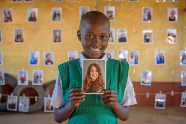 A girl in Kenya holds a photo of her sponsor