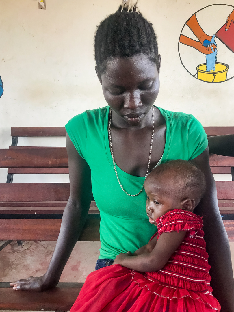 Anjoy Abdallah, 22, holds her 1-and-a-half-year-old daughter, Mary Namato, at Gurei Primary Health Care Center in Juba, South Sudan. Anjoy brought Mary to the clinic to be assessed after three months of sickness that included vomiting, fever, cough, and diarrhea.