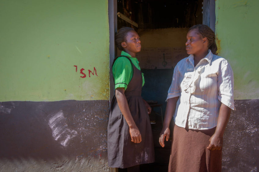 In the doorway of her school in Zambia, Felistus Malyoongo talks with Mapenzi Mweemba, a child protection committee member. Mapenzi and other committee members helped Felisters escape child marriage and return to school.
