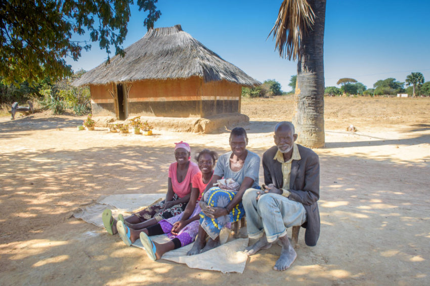Felistus sits outside her aunt's home with her grandmother, Monica; grandfather, Siongeso; and aunt, Evelina Mainza, 55. Her relatives are supportive of Felisters returning to school, but they worry about covering the cost of her education.