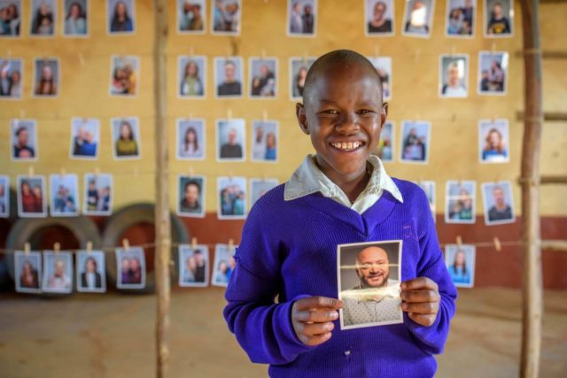 A boy in Kenya holds a photo of a man from Chicago he chose to be his sponsor.