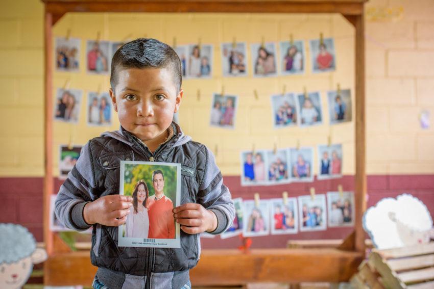 Little boy holds photo of his new Chosen sponsors.