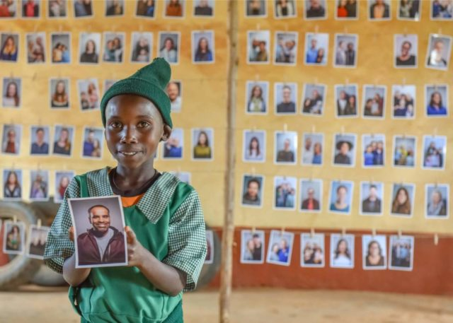 A girl in Kenya holds the photo of a man in Chicago who she chose to be her sponsor.