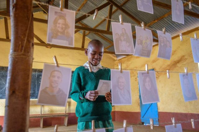 A boy in Kenya chooses a photo of his sponsor off of a line strung with many photos of Americans.