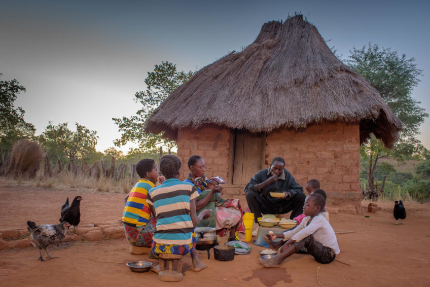 Eunice, 35, and Diyo, 45, and their children share bowls of nshima, corn-flour porridge, for their evening meal. Maize is the staple food and chief cash crop for most Zambians. However, drought is challenging their ability to feed themselves and make an income.