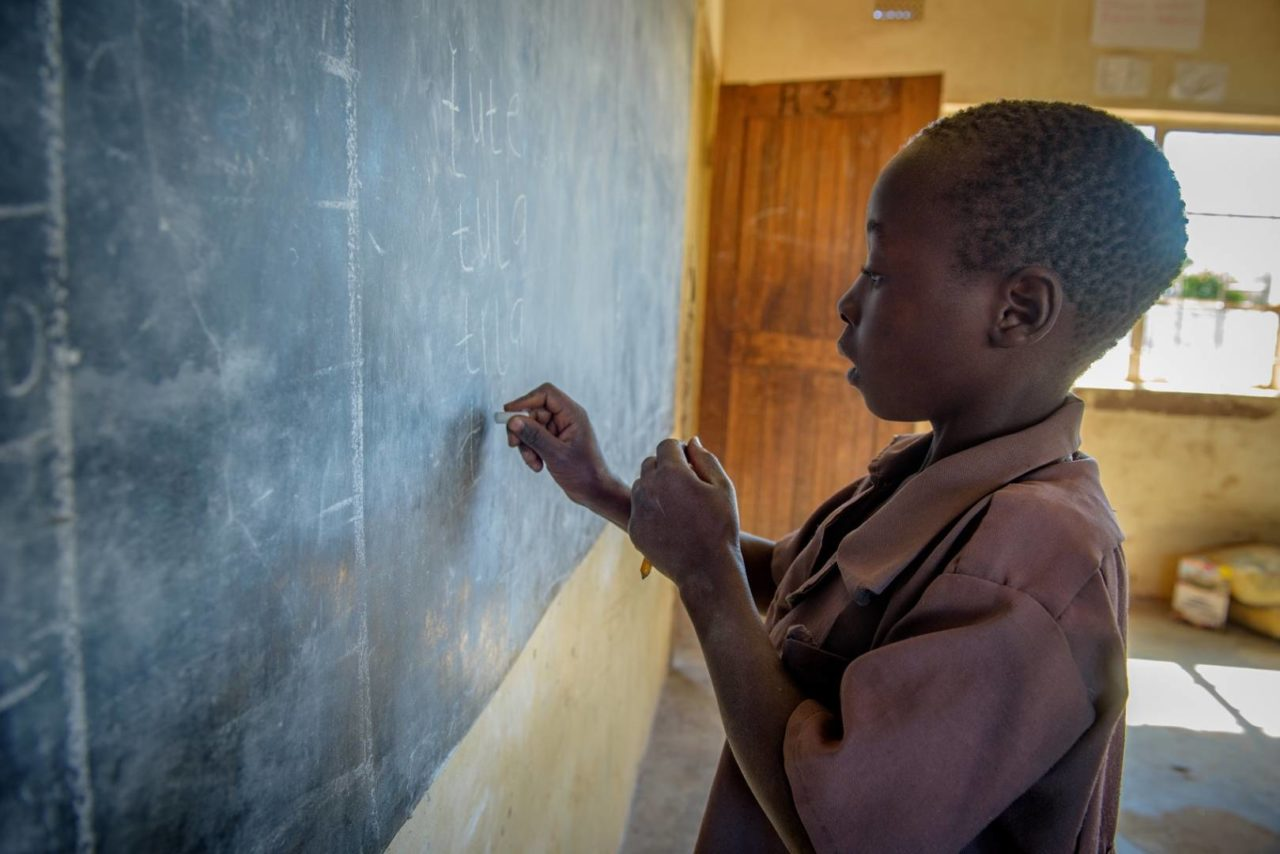 Nathan writes the chalkboard in his primary school class. He wants to be a teacher when he grows up. When it's time to pay school fees, his father can sell a goat to make sure the children can attend school.