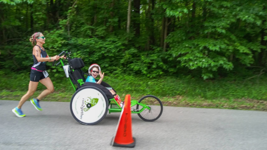 Runner pushes across the finish line 11-year-old athlete in wheelchair.