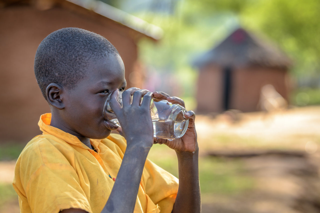 Children drink clean water from a gravity-fed system World Vision installed in Kesot village in Kenya. They used to walk 6 kilometers a day to help bring home dirty water.
