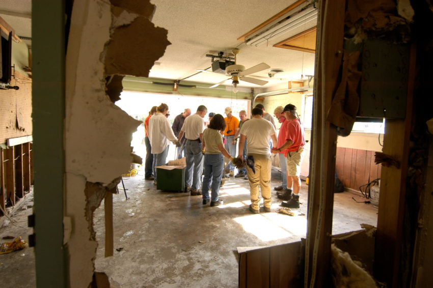 World Vision supported churches in leading post-Katrina recovery. A volunteer work crew organized by a local partner church prays before working on a flood-damaged home in Ocean Springs, Mississippi.