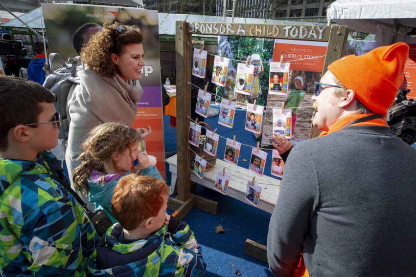 A mother and three children listen to someone in an orange hat talk at an activity station at an event in New York City.