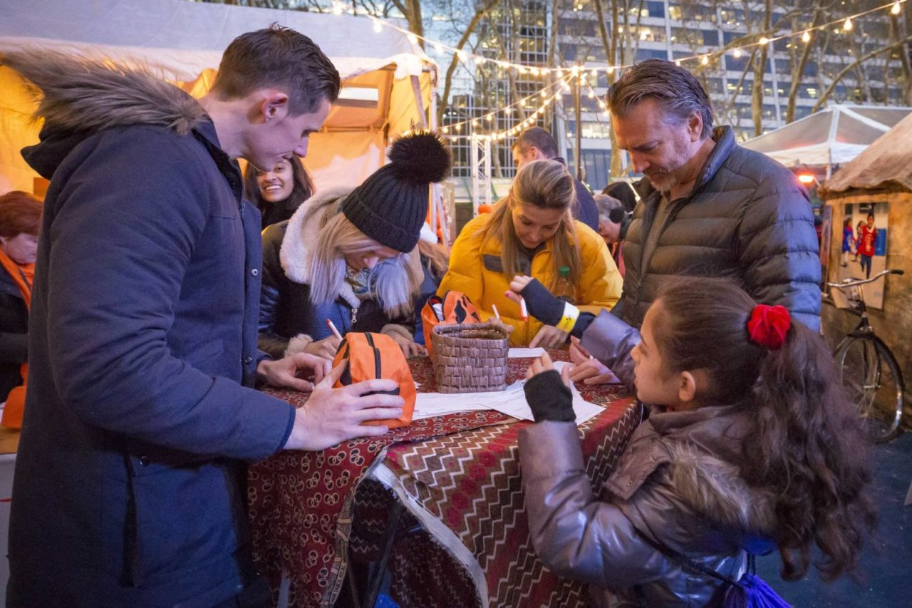People stand at a table and write notes at an activity station at a World Vision event in New York City.