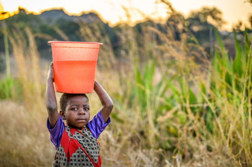 Little girl carries bucket fill of water on her head.