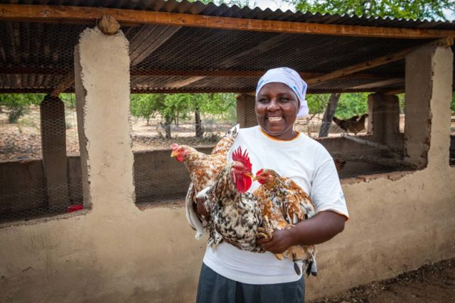 A woman holds chickens.